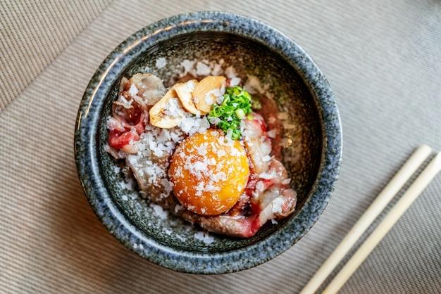 Danie omakase wołowina hakoshima wagyu grillowana na ryżu do sushi z żółtkiem