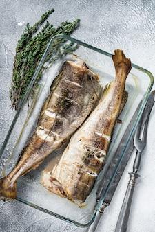 Danie rybne - pieczony dorsz z ziołami w naczyniu do pieczenia. białe tło. widok z góry.