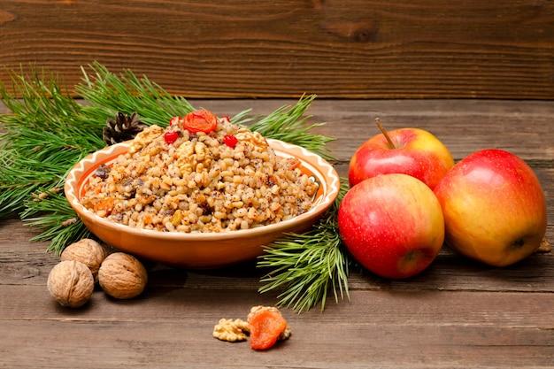 Danie tradycyjnej słowiańskiej uczty w wigilię na brązowym drewnianym stole. gałęzie sosny, jabłka, orzechy włoskie.