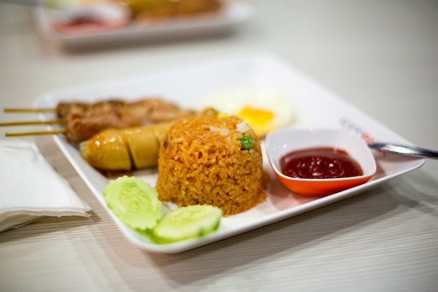 Danie w azjatyckiej restauracji lub kawiarni. pikantny ryż tajski z sosem z kwadratowych talerzy