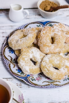 Danie z ciastkami w kształcie pierścienia nad białym drewnianym stołem w pionie