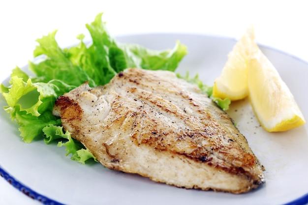Danie z fileta rybnego z sałatą i cytryną na talerzu z bliska