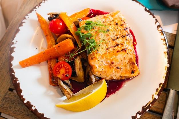 Danie z grillowanego fileta z łososia z warzywami na talerzu.