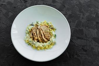 Danie z kawałkami mięsa, makaronem, zielenią, sosem z foie gras i ziemią oliwną