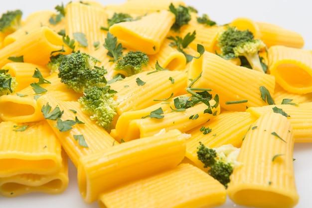 Danie z makaronu paccheri podawane na stole z brokułami