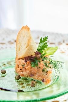 Danie z tatara z łososia, czerwonej i zielonej cebuli, skórki cytryny i oliwy z oliwek podawane na talerzu