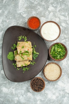 Danie z widokiem z góry w talerzu gołąbki z ziołami w szarym talerzu obok przypraw kwaśna śmietana na szarym stole