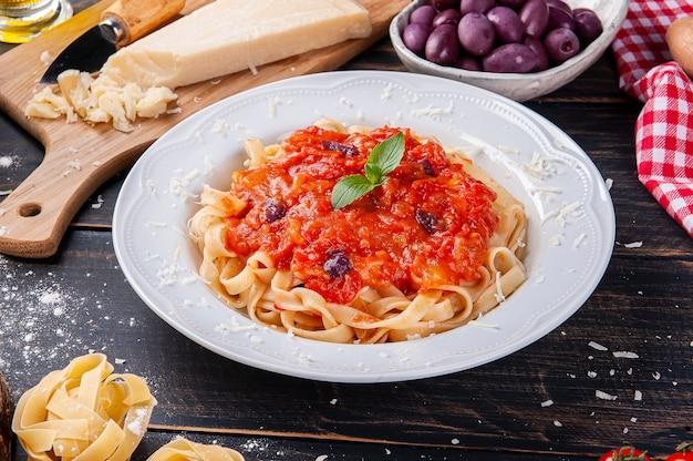 Danie z włoskiego makaronu z sosem pomidorowym. kompozycja ze składnikami do przygotowania potrawy.