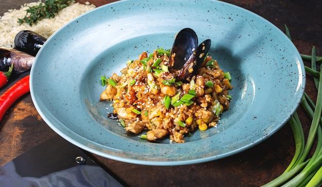 Danie ze smażonego ryżu z kurczakiem i owocami morza