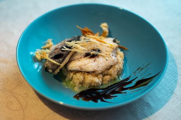 Danie ze smażonej ryby i chipsów parmezanowych na niebieskim talerzu