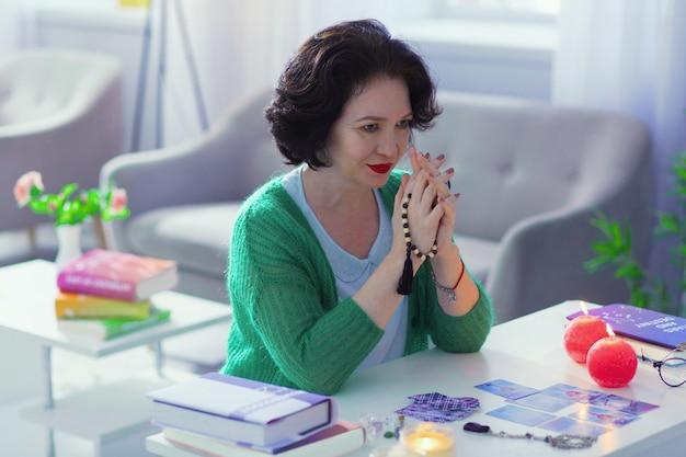 Dar magii. miła, miła kobieta składająca ręce podczas praktykowania magii