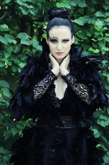 Dark queen w parku. czarna sukienka fantasy.