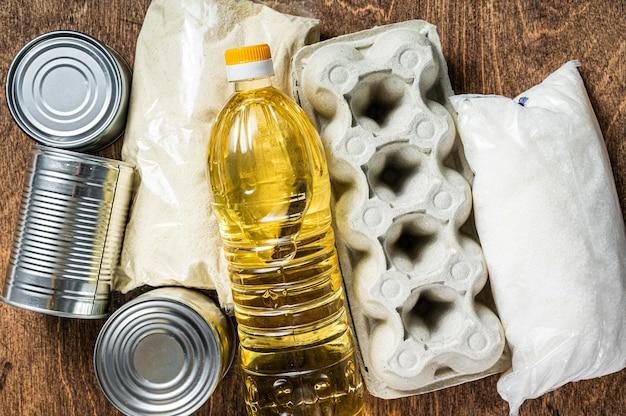 Darowizna dostawy żywności, koncepcja pomocy w kwarantannie. olej, konserwy, makarony, chleb, cukier, jajko. drewniane tło. widok z góry.