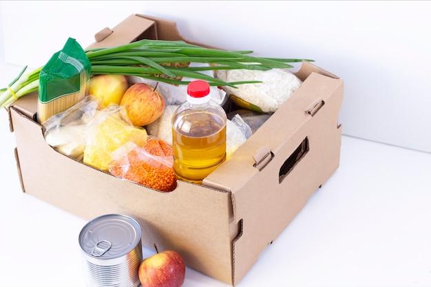 Darowizna. pudełko na zakupy, pomóż produkty potrzebującym. puszka na datki. karton z podstawowymi produktami żywnościowymi na białym tle.