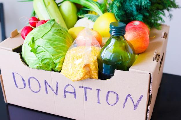 Darowizna żywności. pudełko z owoców i warzyw jabłka kapusta rzodkiewka olej cukinia, grys z bliska.