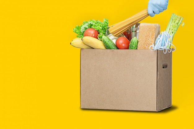 Darowizny pudełko z jedzeniem na żółtym tle. dostawa koronawirusa