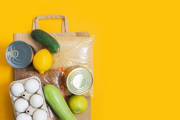 Darowizny żywności na papierowej torbie na żółtej ścianie.