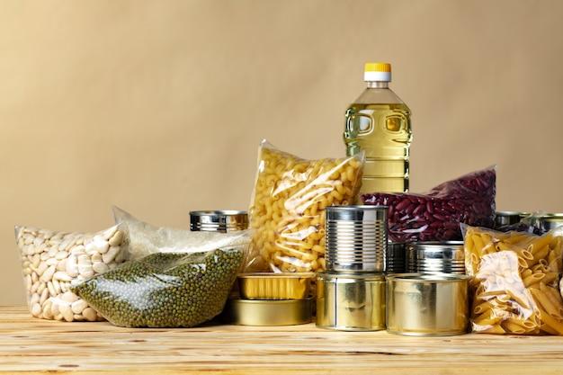 Darowizny żywności z konserw na tle tabeli. przekaż koncepcję. ścieśniać.