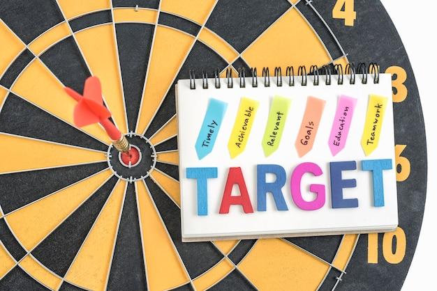 Dart cel w bullseye z wyrazy na notebooka z pisma ręcznego w odpowiednim czasie osiągalne istotne cele edukacji pracy zespołowej nad tłem tarczy, pojęcie sukcesu firmy