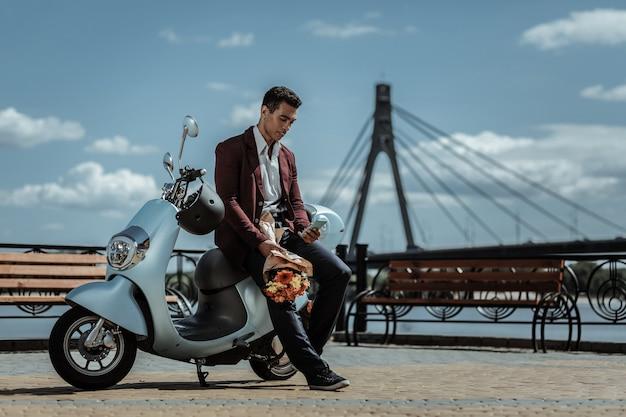 Data wkrótce. niski kąt pozytywnego atrakcyjnego faceta z bukietem kwiatów i opierającego się na motocyklu