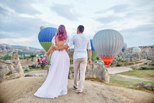 Data zakochanej pary o zachodzie słońca na tle balonów w kapadocji, turcja. mężczyzna i kobieta przytulanie stojąc na wzgórzu i patrzeć na duże balony. zaręczyny w górach kapadocji