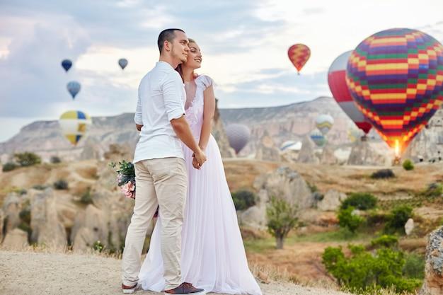 Data zakochanej pary o zachodzie słońca przed balonami w kapadocji