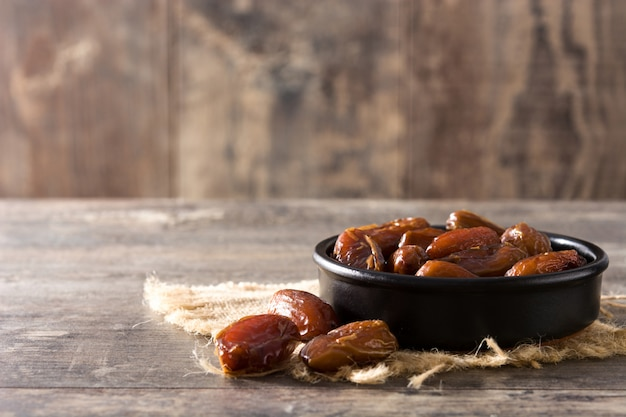 Datuje jedzenie w czarnym pucharze na drewnianej stół kopii przestrzeni