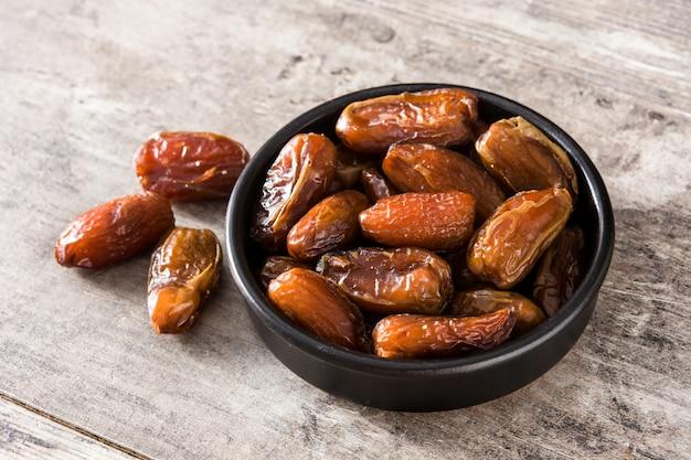 Daty jedzenia w czarnej misce na drewnianym stole