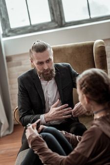 Dawać instrukcje. brodaty doświadczony psycholog udzielający przydatnych instrukcji zestresowanym nastolatkom
