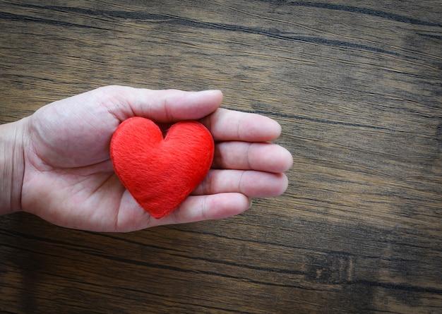 Dawać miłości mężczyzna trzyma czerwonego serce w rękach dla miłości walentynki dbają