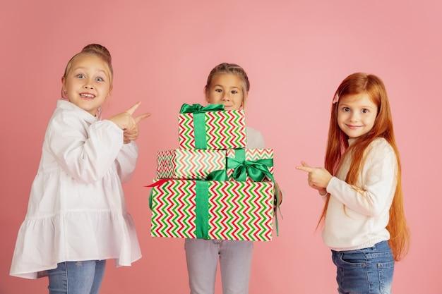 Dawanie i otrzymywanie prezentów na święta bożego narodzenia. grupa szczęśliwych uśmiechniętych dzieci zabawy, świętuje na białym tle na różowym tle studio. spotkanie noworoczne 2021, dzieciństwo, szczęście, emocje.
