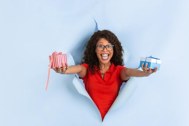 Dawanie prezentów, prezentów. wesoła afro-młoda kobieta w rozdartym niebieskim tle papieru, emocjonalne, ekspresyjne. przełamanie, przełom. pojęcie ludzkich emocji, wyraz twarzy, sprzedaż, reklama.