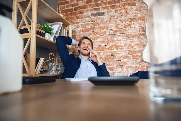 Dawno się nie widzieliśmy, rozmawiam przez telefon. młody mężczyzna, menedżer wraca do pracy w swoim biurze po kwarantannie, czuje się szczęśliwy i zainspirowany. powrót do normalnego życia. koncepcja biznesu, finansów, emocji.