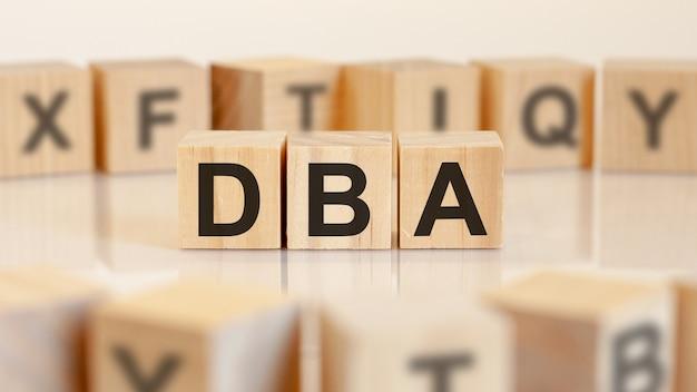 Dba - akronim z drewnianych klocków z literami, administrator bazy danych lub prowadzenie działalności gospodarczej jako skrót pojęcie dba, losowe litery dookoła, żółte tło