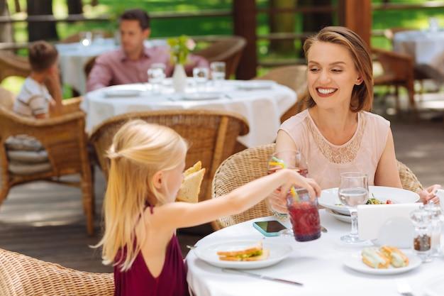 Dbać. atrakcyjna blondynka o blond włosach czuje się niesamowicie szczęśliwa, opiekując się swoją małą córeczką