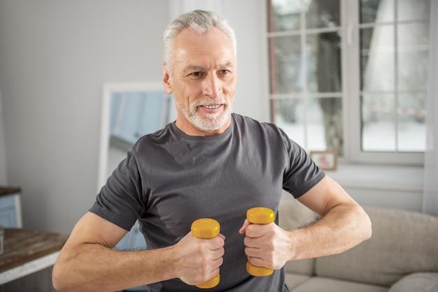 Dbać o kondycję. atrakcyjny dojrzały mężczyzna wyrażający pozytywność podczas porannych ćwiczeń i niecierpliwie wyczekujący