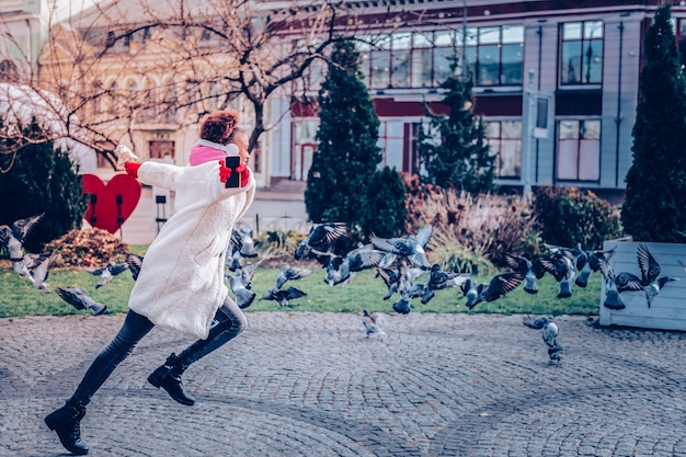 Dbać o kondycję. zachwycona międzynarodowa kobieta podnosząca ręce podczas aktywnego dnia