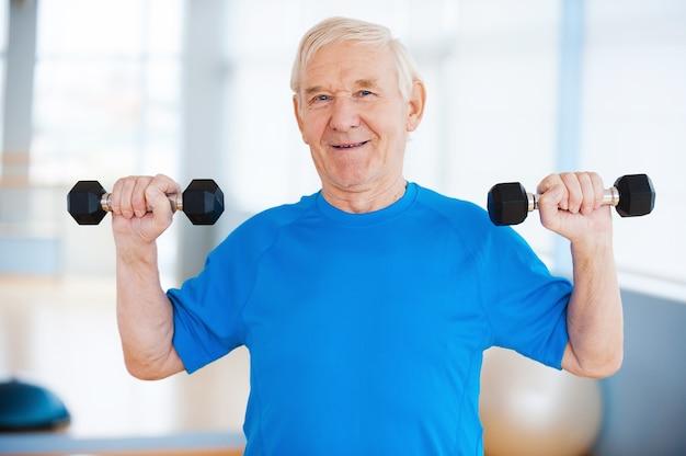 Dbać o zdrowie. szczęśliwy starszy mężczyzna ćwiczący z hantlami i uśmiechający się stojąc w pomieszczeniu