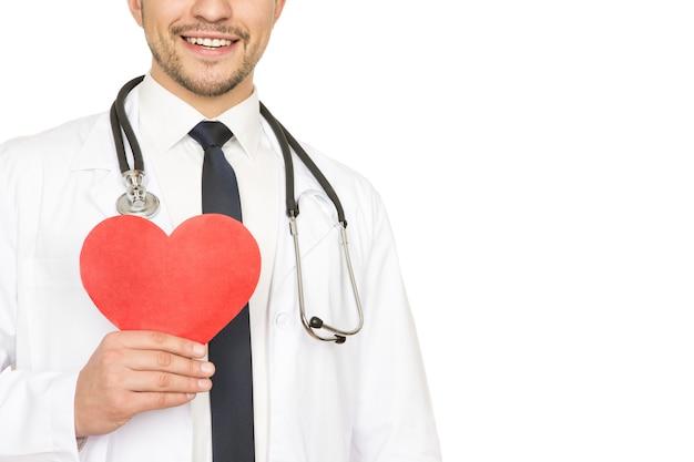 Dbaj o swoje serce. przycięte studio strzał mężczyzny lekarza posiadającego czerwone serce i uśmiechnięty radośnie na białym tle