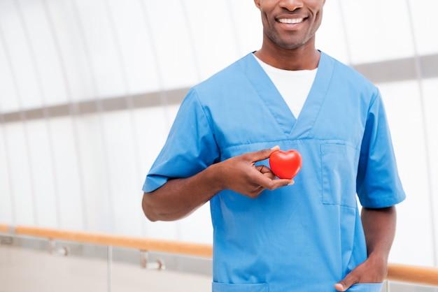 Dbaj o swoje serce. zbliżenie: pewny siebie młody afrykański lekarz w niebieskim mundurze, trzymający w dłoni rekwizyt serca i uśmiechnięty