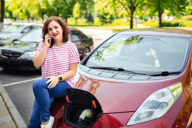 Dbanie o ekologię i środowisko. kobieta podłącz ładowarkę kolektora do samochodu.