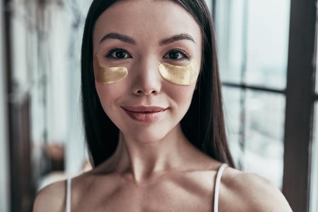 Dbanie o jej skórę. atrakcyjna młoda kobieta używająca opaski na oczy i patrząca w kamerę
