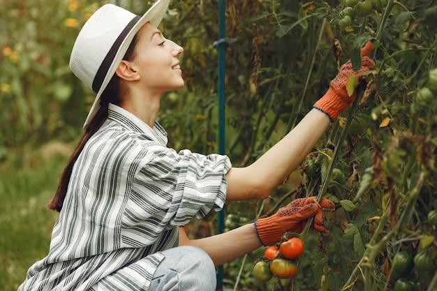 Dbanie o rośliny młoda kobieta. brunetka w kapeluszu i rękawiczkach.