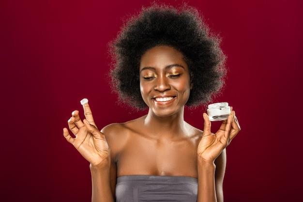 Dbanie o skórę. radosna młoda kobieta uśmiecha się podczas stosowania kremu do twarzy