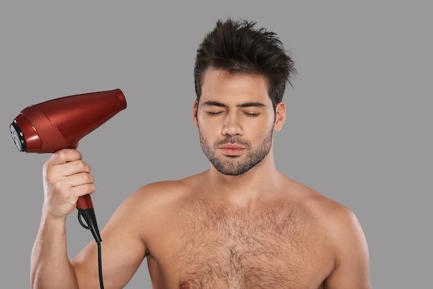 Dbanie o swoje włosy. przystojny młody mężczyzna suszy włosy i ma zamknięte oczy, stojąc na szarym tle