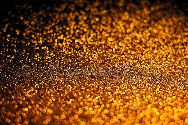 De skupione, tło abstrakcyjnych świateł brokatu. niebieski, złoty i czarny.