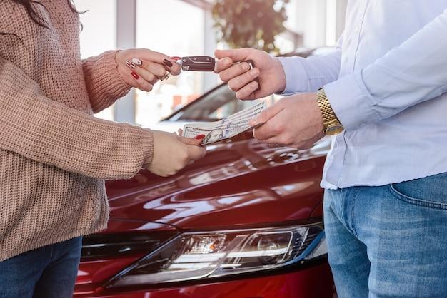 Dealer dający klucze klientowi w salonie;