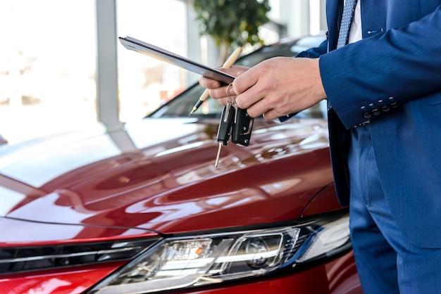 Dealer posiadający klucze od nowego samochodu z bliska