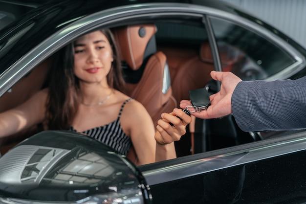 Dealer samochodów daje młodej kobiecie klucz do nowego samochodu