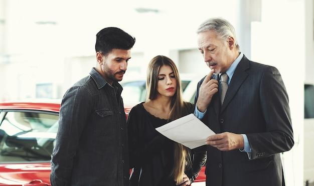 Dealer samochodowy czyta umowę z parą w salonie samochodowym